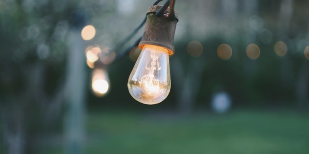 A close up of a bulb in a strand of lights hanging outdoors